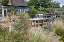 Stipa gigantea, Stipa tenuissima, Verbena bonariensis, Foeniculum vulgare, table and chairs on patio by outdoor kitchen