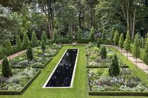 Formal rectangular pool in lawn, box-edged borders, Taxus baccata 'Fastigiata', lupins, agapanthus, Salvia 'Amistad', digitalis, Hydrangea arborescens 'Annabelle', semicircle of Carpinus betulus 'Fast...