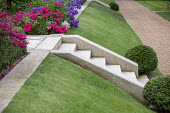 Sloping grass bank, stone steps, clipped Taxus baccata balls, penstemon, Rosa 'Flower Carpet', gravel path