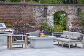 Stone firepit on terrace, contemporary wooden chairs with cushions, archway in brick wall, lavender, outdoor kitchen grill