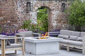 Stone firepit on terrace, contemporary wooden chairs with cushions, archway in brick wall, lavender