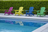 Colourful chairs on swimming pool terrace, Prunus lusitanica hedge