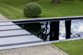 Stepping stones over formal rectangular pond, gravel path, clipped box ball