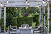 Stone firepit on terrace, contemporary wooden chairs with cushions, Prunus lusitanica hedge, lights on pergola