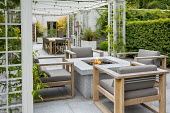 Stone firepit on terrace, contemporary wooden chairs with cushions, pergola, Prunus lusitanica hedge, table and chairs