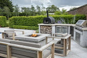 Stone firepit on terrace, contemporary wooden chairs with cushions, outdoor kitchen, pizza oven and grill, Prunus lusitanica hedge