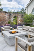 Stone firepit on terrace, contemporary wooden chairs with cushions, arch in brick wall, lavender, Olea europaea