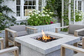 Contemporary firepit surrounded by chairs on patio, Hydrangea arborescens 'Annabelle' in raised bed