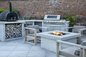 Stone firepit on terrace, contemporary wooden chairs with cushions, outdoor kitchen, pizza oven and grill, brick wall, log store
