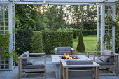 Stone firepit on terrace, contemporary wooden chairs with cushions, Prunus lusitanica hedge