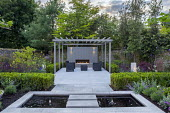 Clipped Buxus sempervirens hedge, Verbena bonariensis, stepping stones over pond, stone paving, grey painted pergola, outdoor fireplace, sofas and table