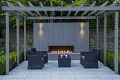 Outdoor sofas under grey painted pergola with fireplace