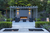 Clipped Buxus sempervirens hedge, stepping stones over formal pond, stone paving, grey painted pergola, outdoor fireplace, sofas and table