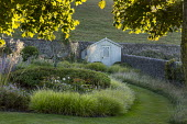Mown grass path, Seseleria autumnalis, Stipa gigantea, wooden shed, Geranium 'Brookside'