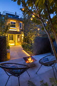 Contemporary chairs and firepit on stone patio, sliding glass doors, multi-stemmed prunus, view into kitchen inside, hanging candle lanterns