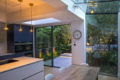 View from inside contemporary kitchen to courtyard garden outside, sliding glass doors, hanging candle lanterns