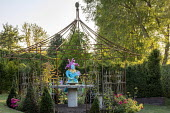 Painted papier-mâché figure in metal arbour, yew pyramids, roses