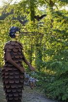 Metal pine cone woman, metal gates