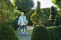 Painted papier-mâché figure in formal garden, yew topiary