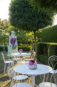 Painted papier-mâché figure and white metal table and chairs on lawn under Robinia pseudoacacia 'Umbraculifera', clipped yew hedge bench