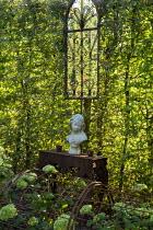 Stone bust on metal table against hornbeam hedge, mirror, living room