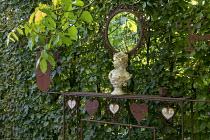 Stone bust on metal fireplace against hornbeam hedge, mirror, living room