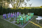 Colourful painted papier-mâché chess set in yew hedge enclosure, bench