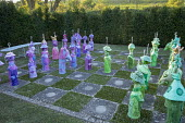 Colourful painted papier-mâché chess set in yew hedge enclosure