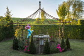 Painted papier-mâché figure in metal arbour, yew pyramids, roses, view to vineyard