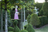 Painted papier-mâché figures in formal garden, box and yew topiary