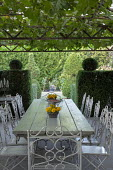 Metal table and chairs on terrace under pergola, yew topiary