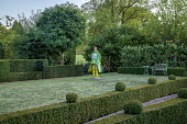 Clipped bench in topiarised yew hedge under Robinia pseudoacacia 'Umbraculifera', white bench, low box hedge, painted papier-mâché figure on lawn, garden 'room'