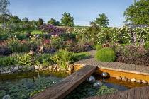 Wooden bridge across water lily pond, pebble edging, rose garden, heuchera, Rosa 'Charles Austin', Rosa 'Munstead Wood', Rosa 'Hugo Maweroff'