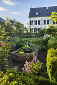 Kitchen garden in clipped box hedge enclosure, woven willow raised beds, chives, lettuces