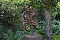 Metal sculpture under tree, roses