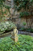 Stone cupid statue on plinth in ivy border, azalea by wall, table and chairs in courtyard