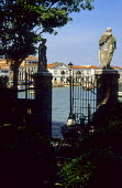 View through gate to canal, statue on plinth