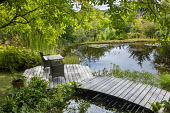 Table and chairs on wooden jetty 'floating' over pond