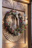 Foraged Christmas door wreath hanging on wooden door, clematis and teasel seedheads, rosehips, ivy, woven willow
