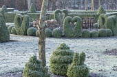Metal bird and fence ornaments in border, clipped Buxus sempervirens heart and snail topiary