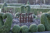Metal bird and fence ornament in border, clipped Buxus sempervirens heart topiary