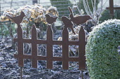 Metal bird and fence ornament in border
