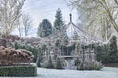 View across frosty lawn to metal pergola, hydrangea seedheads in box-edged border