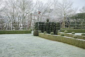 Skittle alley in frost, yew topiary, topiarised box hedge, metal archway
