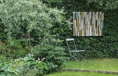 Pyrus salicifolia 'Pendula', hosta, Acanthus spinosus, chair, woodwork panel by Margaret Murton