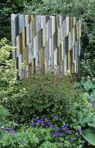 Woodwork panel by Margaret Murton, Geranium phaeum, Pyrus salicifolia 'Pendula', hosta