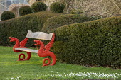 Red dragon bench on lawn by clipped yew hedge, snowdrops