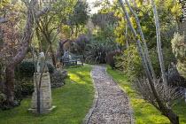 Gravel path, bench on lawn, Phormium 'Pink Stripe', Acacia dealbata, sculpture on stone plinth