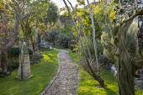 Gravel path, bench on lawn, Phormium 'Pink Stripe', Acacia dealbata, sculpture on stone plinth, red cedar sculpture by Ed Elliott