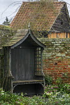 Wooden arbour by brick wall, snowdrops, Helleborus x hybridus